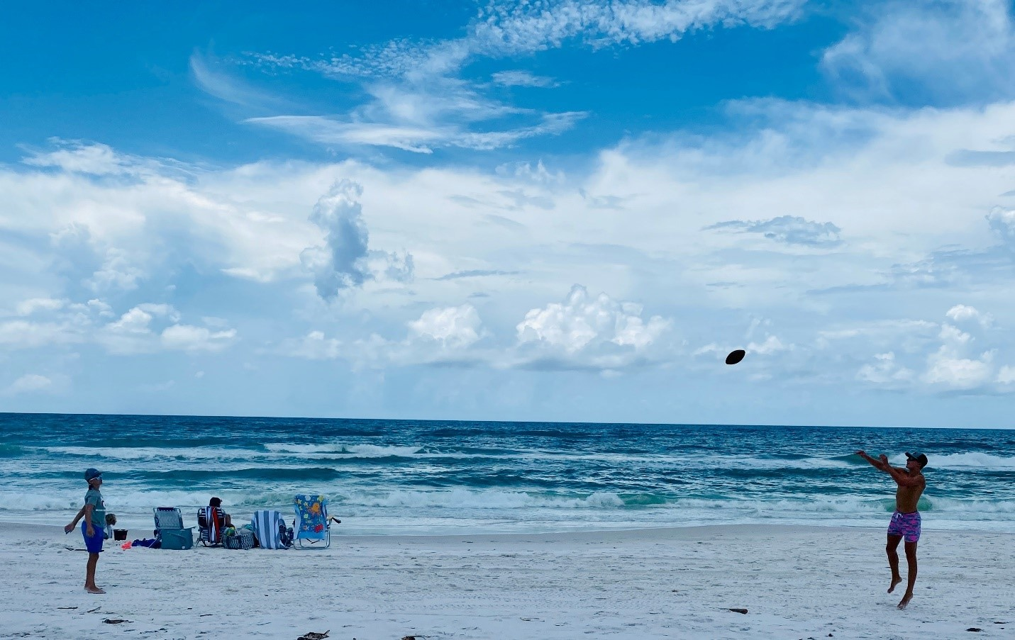 Two men toss a football while another person sits in one of four lawn chairs at the shoreline at Grayton Beach State Park.
